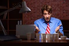Кофе молодого работника выпивая работая вечером перенос стоковые фотографии rf