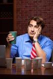 Кофе молодого работника выпивая работая вечером перенос стоковое фото