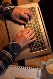 Кофе молодого человека выпивая в кафе и компьтер-книжке использования Укомплектуйте личным составом руки ` s используя компьтер-к Стоковое Изображение