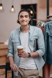 Кофе молодого человека выпивая от бумажного стаканчика и усмехаться на камере Стоковые Фотографии RF