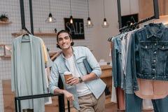 Кофе молодого человека выпивая от бумажного стаканчика и усмехаться на камере в бутике Стоковое Фото