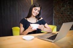 Кофе молодой женщины выпивая и компьютер использования в кафе стоковое изображение