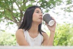 Кофе молодой женщины выпивая от устранимой чашки Азиатская девушка держа кофейную чашку с зеленой природой стоковое фото rf