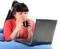 Кофе молодой женщины выпивая перед тетрадью Стоковые Фотографии RF