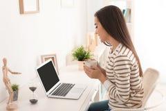 Кофе молодой женщины выпивая пока работающ с компьтер-книжкой на таблице Стоковая Фотография RF