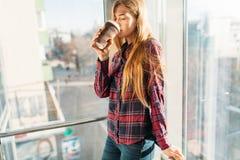 Кофе молодой красивой девушки выпивая, женщина в офисном здании, ярком солнце, стильной современной девушке Стоковое Изображение RF