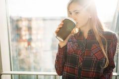 Кофе молодой красивой девушки выпивая, женщина в офисном здании, ярком солнце, стильной современной девушке Стоковая Фотография