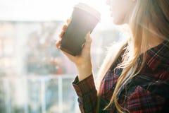 Кофе молодой красивой девушки выпивая, женщина в офисном здании, ярком солнце, стильной современной девушке Стоковые Фото