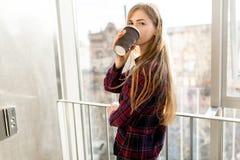 Кофе молодой красивой девушки выпивая, женщина в офисном здании, ярком солнце, стильной современной девушке Стоковое Изображение