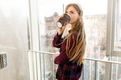 Кофе молодой красивой девушки выпивая, женщина в офисном здании, ярком солнце, стильной современной девушке Стоковые Изображения