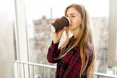 Кофе молодой красивой девушки выпивая, женщина в офисном здании, ярком солнце, стильной современной девушке Стоковое фото RF