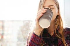 Кофе молодой красивой девушки выпивая, женщина в офисном здании, ярком солнце, стильной современной девушке Стоковые Фотографии RF