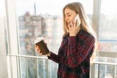 Кофе молодой красивой девушки выпивая и говорить на телефоне, женщине в офисном здании Стоковое Фото