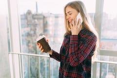 Кофе молодой красивой девушки выпивая и говорить на телефоне, женщине в офисном здании Стоковая Фотография RF