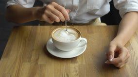 Кофе молодой красивой женщины выпивая в кафе Рука сахара девушки stiring в конце кофе вверх стоковые изображения