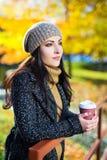 Кофе молодой красивой женщины выпивая в парке осени Стоковое Изображение RF