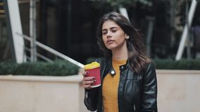 Кофе молодой красивой женщины выпивая и идти на улицу около бизнес-центра видеоматериал