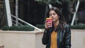 Кофе молодой красивой женщины выпивая и идти на улицу около бизнес-центра акции видеоматериалы