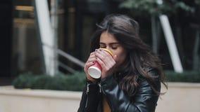 Кофе молодой красивой женщины выпивая и идти на улицу около бизнес-центра сток-видео