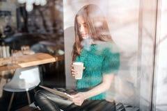 Кофе молодой красивой женщины выпивая на баре кафа Женские модельные детеныши используя цифровую таблетку на кафе Стоковое фото RF