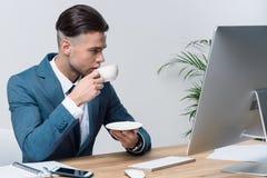 Кофе молодого бизнесмена выпивая пока использующ настольный компьютер в офисе Стоковое Изображение RF