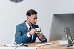 Кофе молодого бизнесмена выпивая пока использующ настольный компьютер в офисе Стоковая Фотография RF