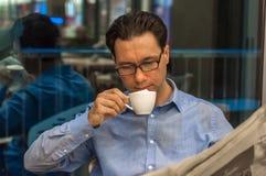 Кофе молодого бизнесмена sipping и газета читать на кафе Стоковые Изображения