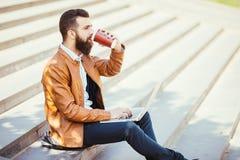Кофе молодого человека битника выпивая на улице и портативном компьютере держать в руке Стоковое Фото