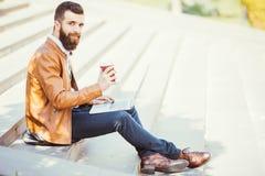 Кофе молодого человека битника выпивая на улице и портативном компьютере держать в руке Стоковое Изображение