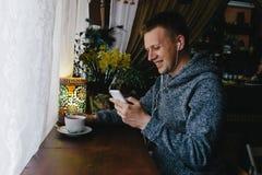 Кофе молодого человека выпивая в кафе и телефоне использования Счастливые детеныши m Стоковое Изображение RF