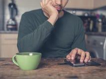 Кофе молодого человека выпивая и использование умного телефона Стоковые Изображения RF