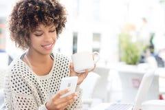 Кофе молодой Афро-американской женщины выпивая Стоковое Изображение RF