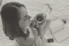 Кофе молодой женщины выпивая в кровати стоковые фотографии rf