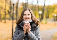 Кофе молодой женщины выпивая в парке осени Стоковая Фотография RF