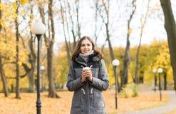 Кофе молодой женщины выпивая в парке осени Стоковые Фотографии RF