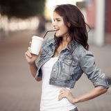 Кофе молодой женщины выпивая от бумажного стаканчика на улице города Стоковая Фотография RF