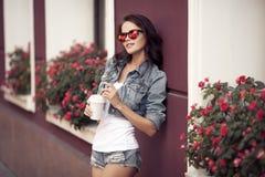 Кофе молодой женщины выпивая от бумажного стаканчика на улице города Стоковое фото RF