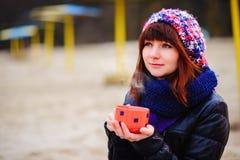 Кофе молодой женщины выпивая от ее thermos, наслаждаясь вечером осени морем Стоковые Фотографии RF