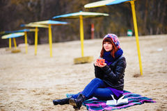 Кофе молодой женщины выпивая от ее thermos, наслаждаясь вечером осени морем Стоковое фото RF