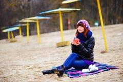 Кофе молодой женщины выпивая от ее thermos, наслаждаясь вечером осени морем Стоковое Изображение RF