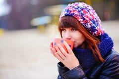Кофе молодой женщины выпивая от ее thermos, наслаждаясь вечером осени морем Стоковое Фото