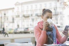 Кофе молодой женщины выпивая пока использующ сотовый телефон на кафе тротуара Стоковая Фотография RF
