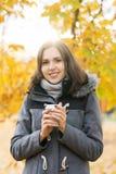 Кофе молодой и красивой девушки выпивая в парке осени Стоковая Фотография RF