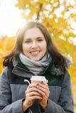 Кофе молодой и красивой девушки выпивая в парке осени Стоковые Изображения RF