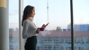 Кофе молодой красивой бизнес-леди выпивая и сообщения посылки готовя панорамное окно в европейское современном сток-видео
