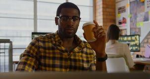 Кофе мужского график-дизайнера выпивая и ноутбук 4k использования видеоматериал
