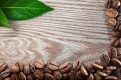 Кофе на деревянной предпосылке с зелеными листьями Стоковое фото RF