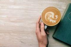 Кофе на деревянной таблице с книгой держит вручную Стоковые Изображения RF