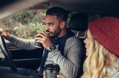 Кофе пар выпивая пока управляющ автомобилем Стоковое Изображение
