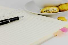 Кофе, печенья, тетрадь и ручка Стоковые Фото